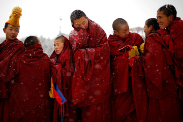 "Tibetan monks attend a ceremony at the Langmu Lamasery during the ""Sunbathing Buddha Festival"", in Gannan Tibetan Autonomous Prefecture"