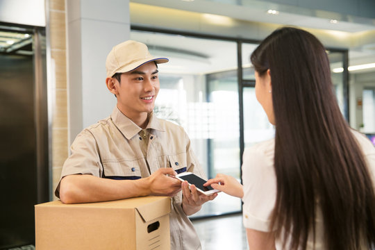 Delivery man showing smartphone to woman at reception