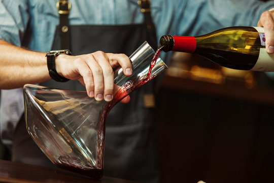 Sommelier pouring red wine into carafe to make perfect color