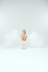 beautiful woman with angel wings doing praying gesture and looking at camera isolated on white