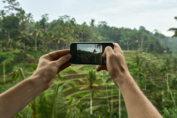 Man shooting photo on terraced rice fields background on Bali