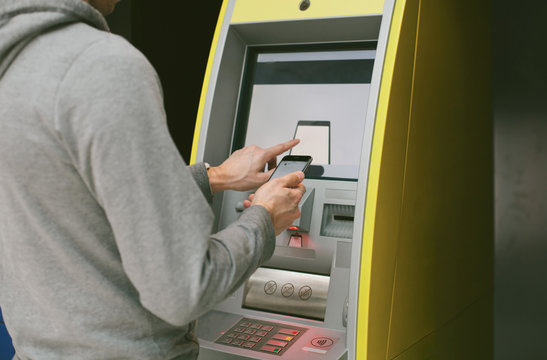 Closeup of male hands using smart phone while typing on screen on ATM, bank machine for cash money withdrawal.