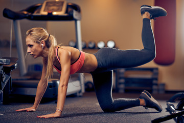 Young Caucasain blonde woman with ponytail and in sportswear doing exercises on the gym floor.