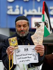 Palestinian demonstrator holding a copy of Koran takes part in a protest against an Israeli decision to trim funds over prisoner stipends, in Hebron, in the Israeli-occupied West Bank