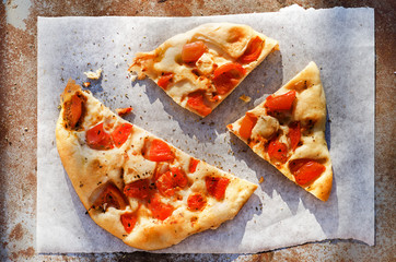 Slices of pizza with tomatoes on rustic background.