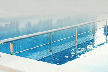 swimming pool with blue water ready to use in the foggy summer morning, with space for text