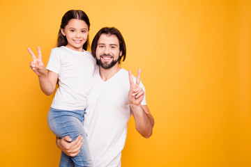 Portrait of her she his he nice cute sweet lovely attractive cheerful people dad holding in hands pre-teen girl showing v-sign isolated over shine vivid pastel yellow background
