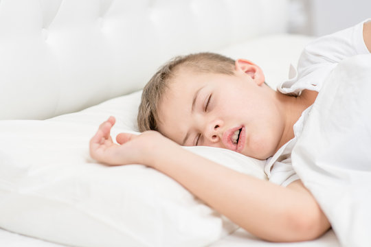 Young boy is sleeping with his mouth open, snoring
