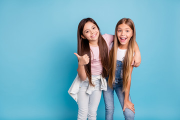 Portrait of two people nice cute lovely charming dreamy attractive cheerful straight-haired pre-teen girls siblings showing aside ad promotion copy space isolated on blue turquoise background