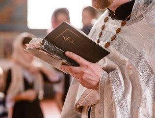 Closeup priest reads bible during church ceremony