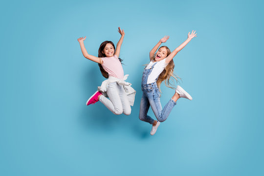 Full length body size view of two people nice-looking crazy lovely attractive cheerful carefree straight-haired pre-teen girls having fun great weekend time overjoy isolated over blue pastel