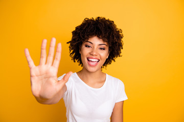 Close up photo beautiful amazed she her dark skin lady glad arms hands five fingers raised show countable uncountable things lesson wearing casual white t-shirt isolated yellow bright background