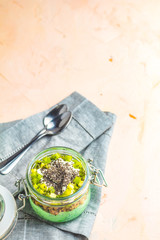 Chia seed pudding with matcha green tea on pink concrete background
