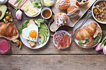 Breakfast food table. Festive brunch set, meal variety with fried egg, croissant sandwich, granola and smoothie. Overhead view