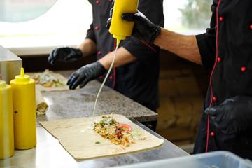 Man at the kitchen cook kebab