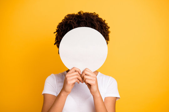 Close up photo beautiful amazing she her dark skin lady hiding face round circle banner placard do not want be recognized wear casual white t-shirt isolated yellow bright vibrant vivid background