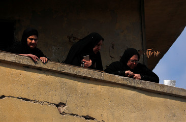 Women watch the funeral of Egyptian police officer Mahmoud Abou El Yazied who was killed in a blast, in Cairo