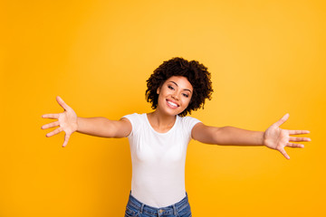 Close up photo cheerful beautiful amazing she her dark skin lady spread hands arms come here to us calling in hugs sweetheart wear casual white t-shirt isolated yellow bright vibrant background