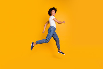Full length body size side profile photo jumping high beautiful she her lady rushing black friday sale shopping store mall wearing casual jeans denim white t-shirt clothes isolated yellow background