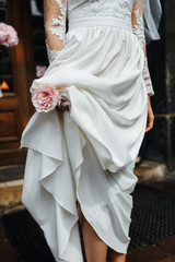 Wedding details. Bride holds tender pink bouquet in her arms. No face