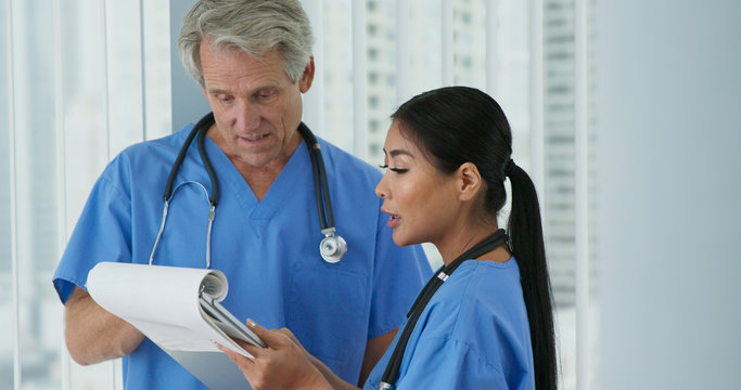 Two friendly medical professionals wearing blue scrubs working together. Medium shot of Japanese woman doctor and Caucasian male nurse going over paperwork in hospital