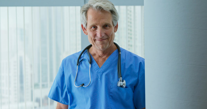Portrait of Senior Caucasian male nurse or doctor looking at camera while standing in hospital. Trustworthy medical professional in blue scrubs with stethoscope smiling in clinic