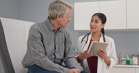 Primary care doctor explaining medical issue to senior male patient in exam room. Female medical professional with tablet computer talking to older man about his health
