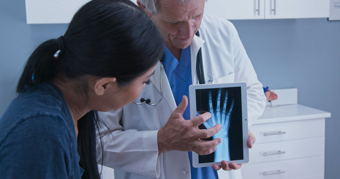 Doctor using tablet computer with x-ray of hand to talk about arthritis with young patient. Senior Caucasian male medical professional with screen demonstrating joint injury to woman
