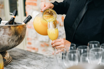 Woman pours orange juice in a glass