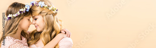beautiful woman and adorable child in colorful floral wreaths hugging face to face with closed eyes on yellow background with copy space