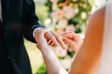 Bride puts wedding ring on groom's finger. No face
