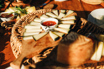 Table with snacks. Different kinds of cheese lie on the wooden board with sauces