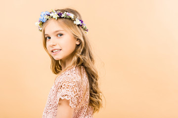adorable child in elegant lacy dress and floral wreath smiling and looking at camera on yellow background
