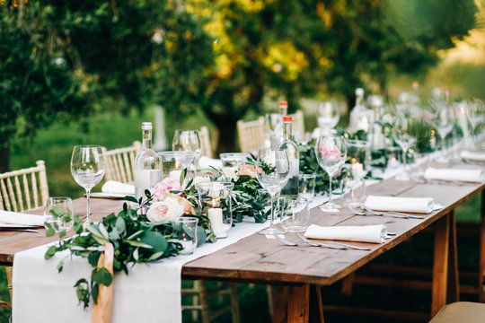 Floral garland of eucalyptus and pink flowers lies on the table for wedding reception. Italian dinner