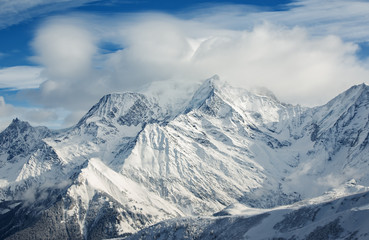 The snow-covered alpine mountain peaks in clouds