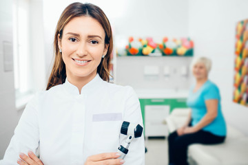Doctor dermatologist with dermatoscope, smiling while looking at camera. Behind her sitting senior patient.