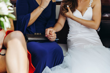 Bride holds woman's hand sitting at the table