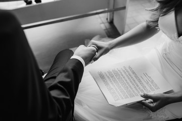 Bride and groom hold each other hands tender sitting with their oathes printed on the paper
