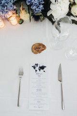 Wedding table setting. Menu card lies between fokr and knife on a white dinner table with blue flowers