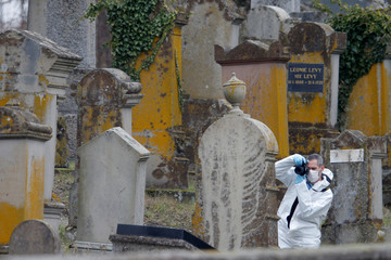 A French gendarme conducts their investigation as he examines graves that were desecrated with swastikas in the Jewish cemetery in Quatzenheim