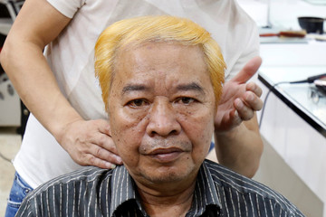 Le Phuc Hai, 66, poses with his dyed hair in U.S. President Donald Trump style in a salon in Hanoi