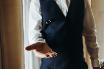 Groom holds wedding ring standing before the window in a hotel room