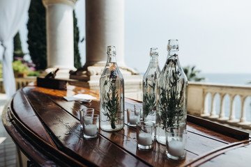 Table decor. Bottles with greenery and glasses with candles stand on the table with great sea view behind