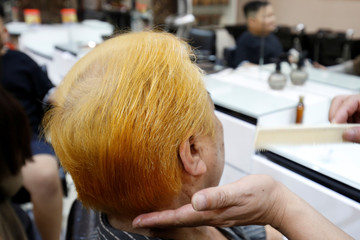 Le Phuc Hai, 66,  gets his dyed hair combed in U.S. President Donald Trump style in a salon in Hanoi