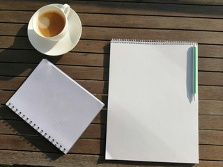 notebook and cup of coffee on wooden table