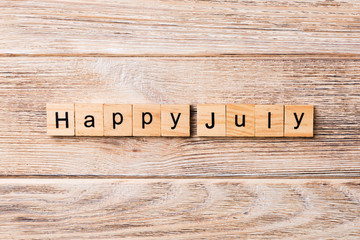 Happy july word written on wood block. Happy july text on table, concept