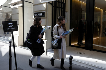 Women hold white roses as they arrive outside the Chanel fashion boutique after news that German haute-couture designer Karl Lagerfeld, artistic director at Chanel and an icon of the global fashion industry for over half a century, has died, in Paris