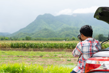 Young man sits in the car trunk take photo with dslr camera with green corn field and mountain nature background. Summer vocation with car on the road concept.