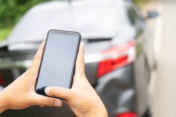 Man Hand Taking Photo Of Car Accident Through Smartphone, close up..Insurance agent using smart phone to take a photo photographing vehicle of damage car crash.