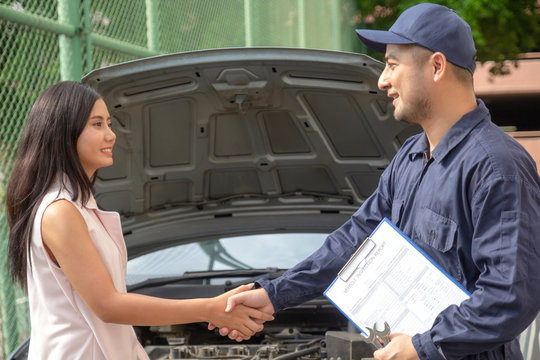 auto service shaking hands with female customer finish work. Car repair and maintenance Insurance concept. mechanic man in uniform and client shake handsin car workshop station, garage automobile shop